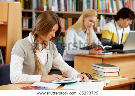 Portrait of clever students preparing lessons in college library - stock photo