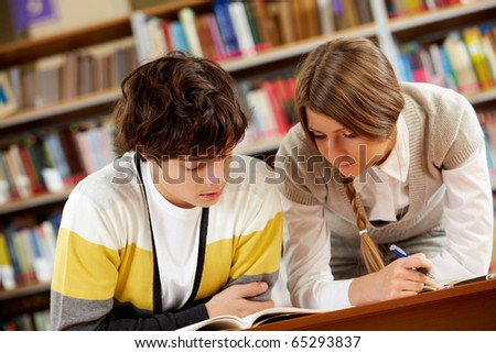Portrait of clever students reading book in college library - stock photo
