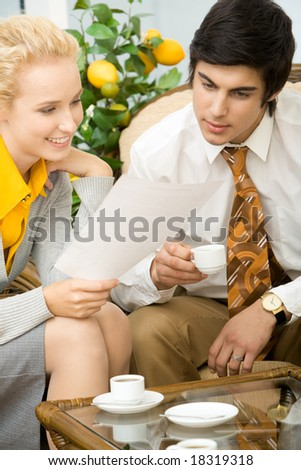 Portrait of co-workers reading business document at meeting - stock photo