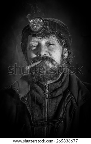 Portrait of coal miner with beard smoking cigar - stock photo