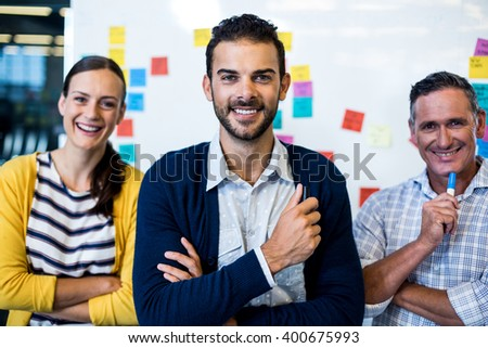 Portrait of colleagues smiling at camera in the office - stock photo