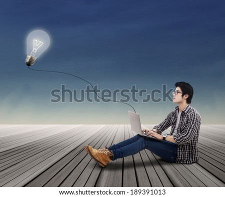 Portrait of college student looking at lit bulb with laptop outdoor - stock photo