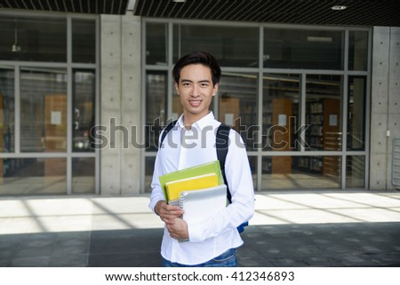 Portrait of college student standing holding book at campus - stock photo