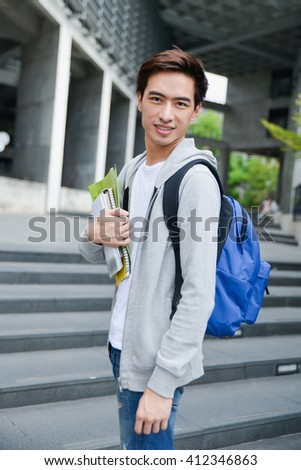 Portrait of college student standing holding book at his university - stock photo