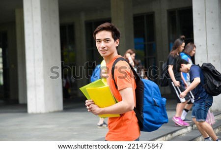 Portrait of college student working holding book at college - stock photo
