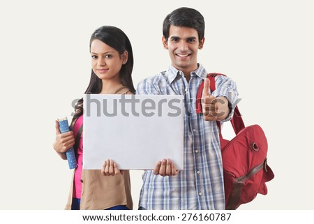Portrait of college students holding a white board - stock photo