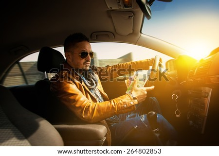 Portrait of concentrated man driving car with a lot of money EUR in hand. Inside photo - stock photo