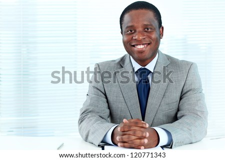 Portrait of confident African businessman looking at camera in office - stock photo