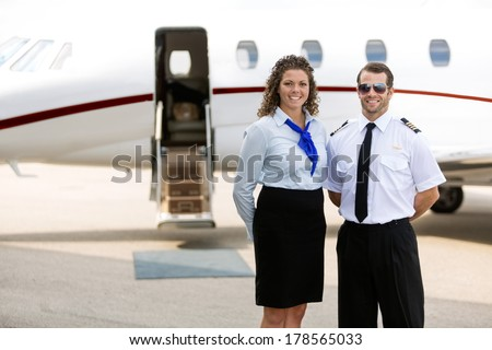 Portrait of confident airhostess and pilot standing against private jet - stock photo