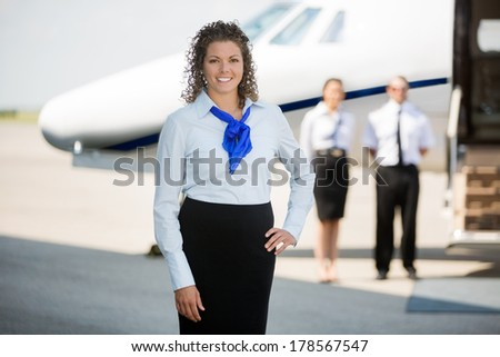 Portrait of confident airhostess with hand on hip standing at airport terminal - stock photo