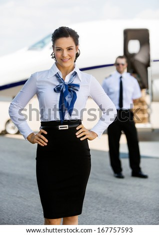 Portrait of confident airhostess with hands on hip against pilot and private jet at airport terminal - stock photo