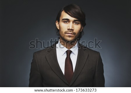 Portrait of confident and attractive male model in business suit looking at camera. Mixed race businessman against black background. - stock photo