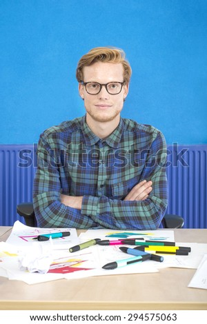 Portrait of confident artist sitting with arms crossed at desk in creative office - stock photo