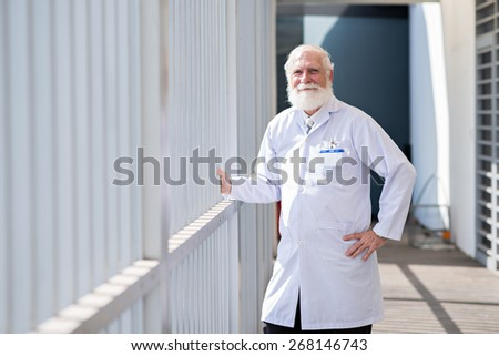 Portrait of confident bearded researcher in lab coat - stock photo