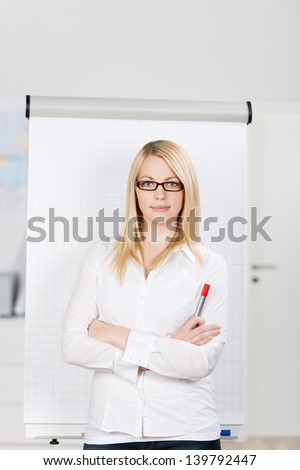 Portrait of confident blond young woman standing by flip chart in office, arms crossed - stock photo