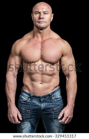 Portrait of confident bodybuilder man standing against black background - stock photo