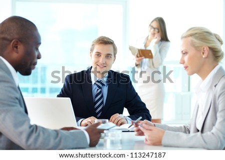 Portrait of confident boss listening to his partners at meeting - stock photo
