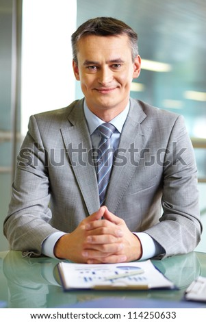 Portrait of confident boss looking at camera at workplace - stock photo
