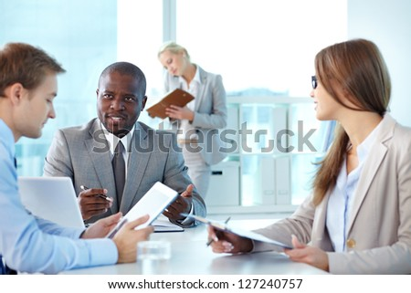 Portrait of confident boss looking at employee during interaction at meeting - stock photo