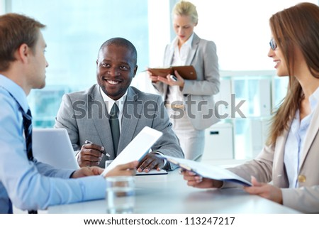 Portrait of confident boss smiling while interacting with employees at meeting - stock photo