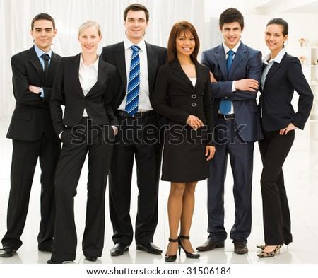 Portrait of confident business group standing in row and looking at camera - stock photo