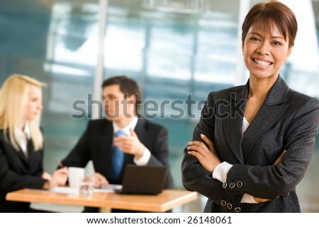 Portrait of confident business leader with working team communicating at background - stock photo