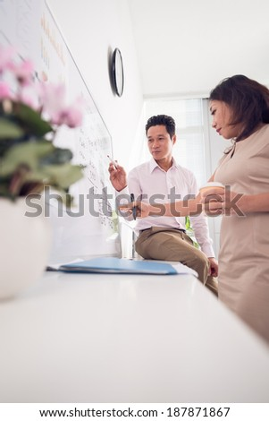 Portrait of confident business partners discussing ideas on whiteboard in office - stock photo