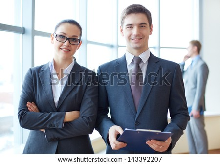Portrait of confident business partners looking at camera with calling employee behind - stock photo