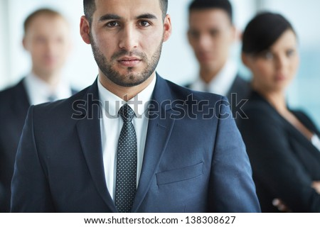 Portrait of confident business partners looking at camera with serious leader in front - stock photo