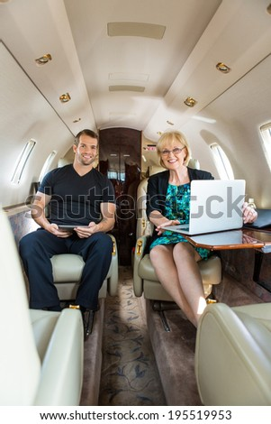 Portrait of confident business people with laptop and digital tablet in corporate jet - stock photo