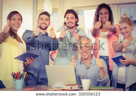 Portrait of confident business people with technologies showing thumbs up in creative office - stock photo