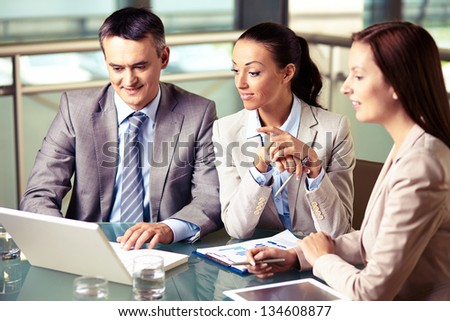 Portrait of confident business team looking at laptop display at meeting - stock photo