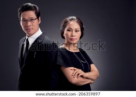 Portrait of confident business team on dark background - stock photo