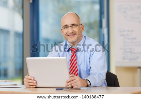 Portrait of confident businessman holding laptop at office desk - stock photo