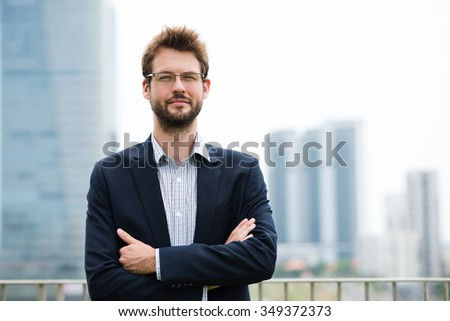 Portrait of confident businessman in glasses standing with his arms folded - stock photo