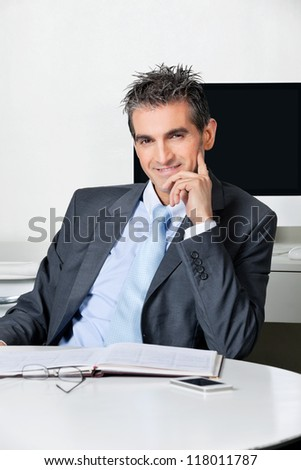 Portrait of confident businessman sitting at desk in office - stock photo