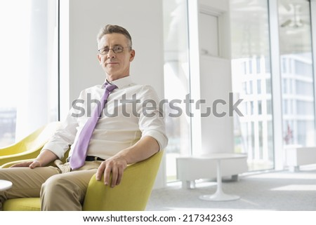 Portrait of confident businessman sitting at office lobby - stock photo