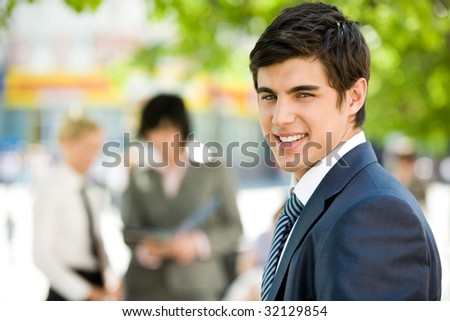 Portrait of confident businessman smiling at camera in a natural environment - stock photo