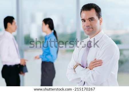 Portrait of confident businessman standing with his arms crossed - stock photo