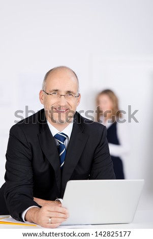 Portrait of confident businessman using laptop with coworker in background at office - stock photo