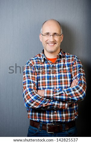 Portrait of confident businessman with arms crossed standing against gray wall - stock photo