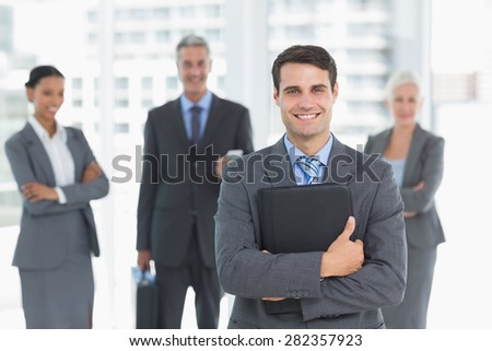 Portrait of confident businessman with colleagues behind in office - stock photo