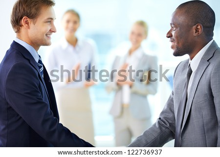 Portrait of confident businessmen handshaking and their colleagues applauding on background - stock photo