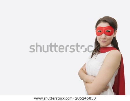Portrait of confident businesswoman dressed as superhero standing arms crossed in office - stock photo