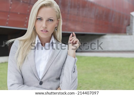 Portrait of confident businesswoman gesturing against office building - stock photo