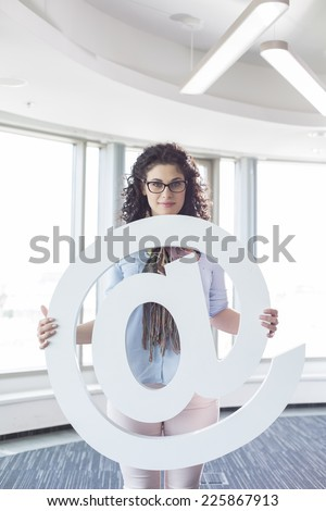 Portrait of confident businesswoman holding at symbol in creative office - stock photo