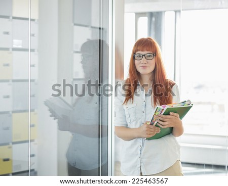 Portrait of confident businesswoman holding files in creative office - stock photo