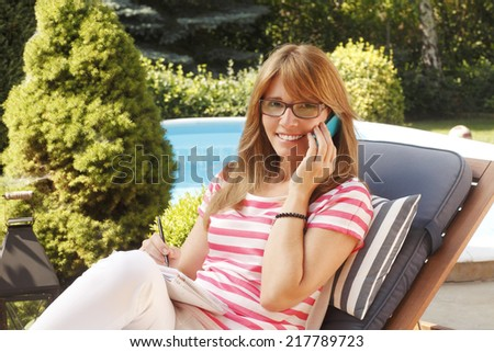 Portrait of confident businesswoman sitting at home and working. - stock photo