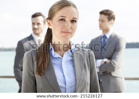 Portrait of confident businesswoman standing with coworkers in background on terrace - stock photo
