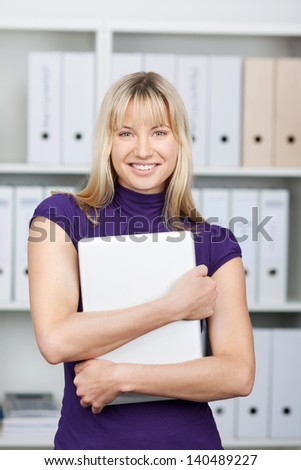 Portrait of confident businesswoman with laptop standing against shelves in office - stock photo